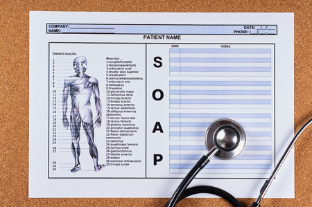 Patient SOAP note sheet, stethoscope on corkwood background. Flat lay.