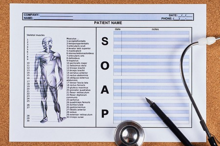 Patient SOAP note sheet, stethoscope and pen on corkwood background. Flat lay.