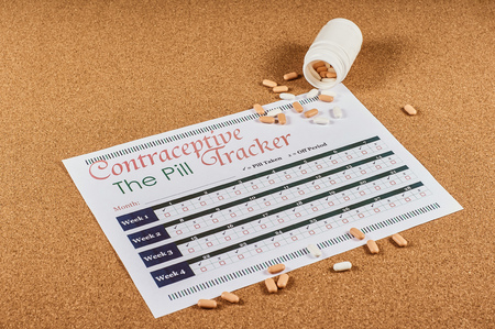 Contraceptive tracker sheet and pills on corkwood background.
