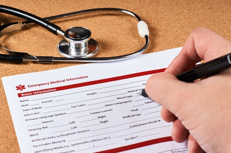Human fill a Emergency medical information form on corkwood and stethoscope background. Close-up. Stock fotó