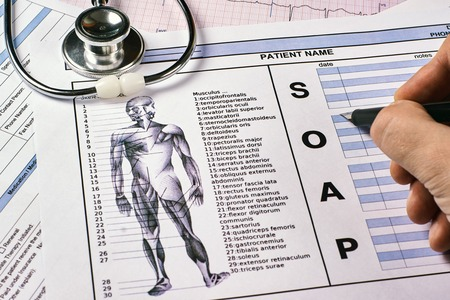 Human fill a Patient SOAP note sheet, stethoscope on corkwood background. Flat lay.