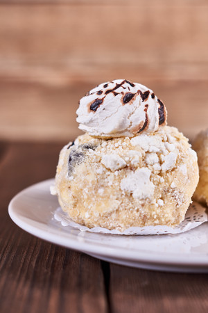 Two airy desserts with meringue in chocolate drops with prunes and butter cream in a white plate on a wooden background