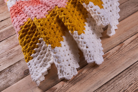 Needlework. Colorful woolen crocheted bedspread on a wooden background. Close-up. Stock Photo