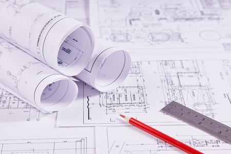 Technische achtergrond. Bouwtekeningen van gebouwen en constructies naast liniaal en rood potlood. Detailopname. Stockfoto