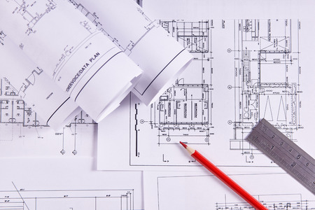 Engineering background. Construction drawings of buildings and structures next to ruler and red pencil. Close-up.