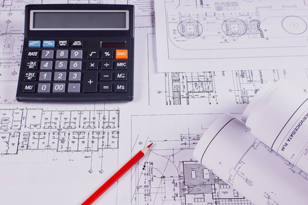 Engineering background. Construction drawings of buildings and structures next to red pencil and calculator. Close-up.