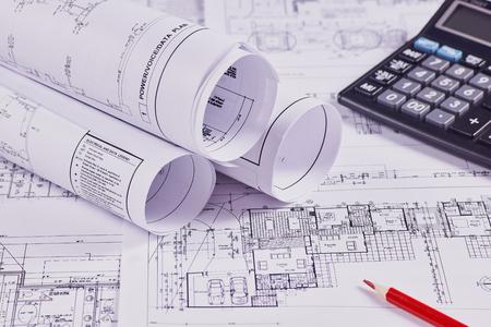 Sfondo di ingegneria. Disegni costruttivi di edifici e strutture accanto a matita rossa e calcolatrice. Avvicinamento.