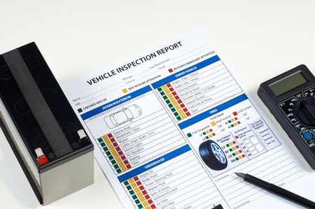 Formulario de informe de inspección de vehículos con multímetro, bolígrafo y batería sobre fondo blanco. Foto de archivo