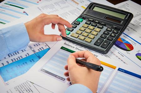 human hands write balance sheet summary on a background balances sheets with calculator