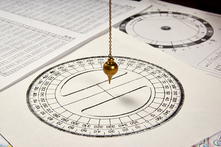 Astrological pendulum for tarot and astrological circle on the background of astrological sheets Stock Photo
