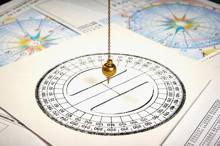 Pendule astrologique pour tarot et cercle astrologique sur fond de cartes astrologiques et horoscopes