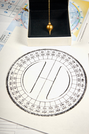 Astrological pendulum for tarot and astrological circle on the background of astrological charts and horoscopes Stock Photo