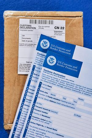 I moduli di dichiarazione doganale si trovano sul pacco con il modulo di dichiarazione doganale CN22 su uno sfondo di velluto blu. Vista generale.