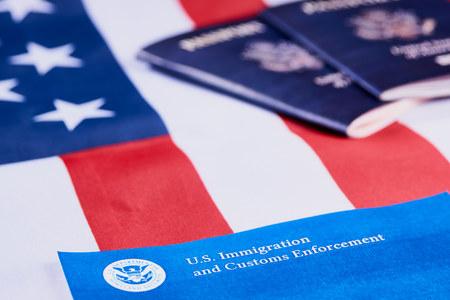 Banner mit Schriftzug der US-Einwanderungs- und Zollbehörde neben amerikanischen Pässen auf dem Hintergrund der amerikanischen Flagge.