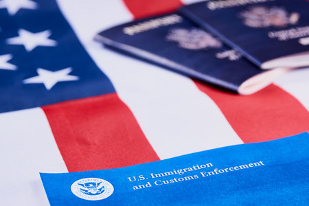 Banner with lettering US Immigration and Customs enforcement next to American passports on American flag background. Foto de archivo