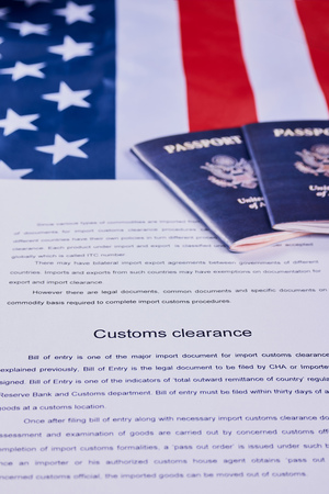 Page of paper with words Customs Clearance next to American passports on American flag background Reklamní fotografie