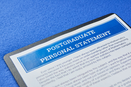 Page of paper with information postgraduate personal statement on a blue velvet background. Close-up