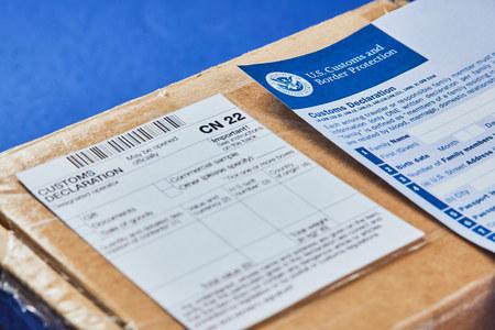 Il modulo di dichiarazione doganale si trova sul pacco con il modulo di dichiarazione doganale CN22 su uno sfondo di velluto blu. Avvicinamento. Archivio Fotografico