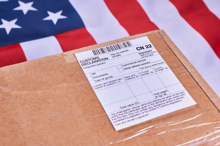 Pacco con modulo di dichiarazione doganale CN22 su sfondo bandiera americana. Avvicinamento