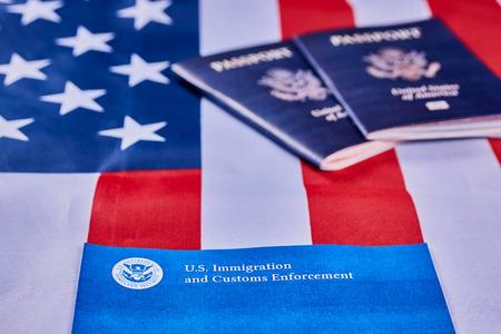 Banner mit Schriftzug der US-Einwanderungs- und Zollbehörde neben amerikanischen Pässen auf dem Hintergrund der amerikanischen Flagge. Standard-Bild