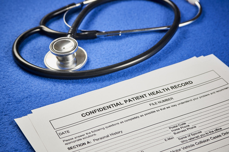 Confidential patient health record next to phonendoscope on a blue velvet background. Close-up