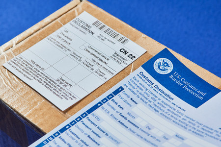 Customs Declaration Form lies on Parcel with Customs declaration form CN22 on a blue velvet background. Close-up.