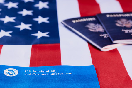 Banner with lettering US Immigration and Customs enforcement next to American passports on American flag background. Фото со стока