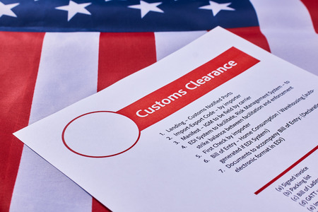 Page with the rules of customs clearance on American flag background. Close-up