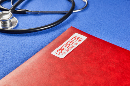 Red folder with the words Confidential for internal use only, next to phonendoscope on a blue velvet background. Close-up