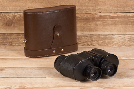 Old army binoculars with a case on a wooden background