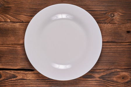 Empty white plate on wooden brown background. Flat lay Stock fotó