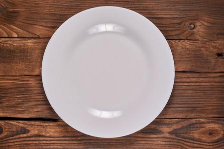 Pusty biały talerz na drewnianym brązowym tle. Płaskie ułożenie Zdjęcie Seryjne