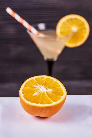 Sliced orange next to martini goblet with fresh orange juice and orange slice, cocktail tube, on a dark wooden background. Focus on orange.