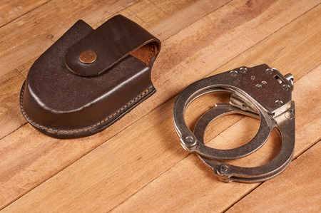 police handcuffs with case on wooden background