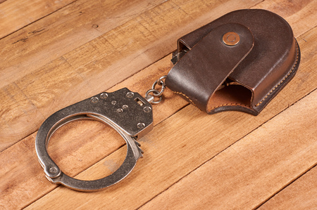 police handcuffs with case on wooden background Stock Photo