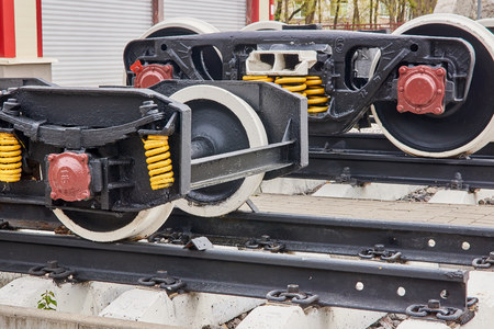 Railway wheels narrow gauge railway and ordinary railway. Freight cargo train or boxcar chassis, suspension and metal wheels stand on the rails, close-up