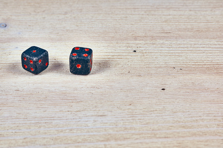 Game dice made of natural stone lie on a white wooden background. Close-up