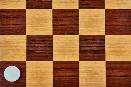 Ein Marmor-Checker auf einem hölzernen Schachbrett. Flach legen