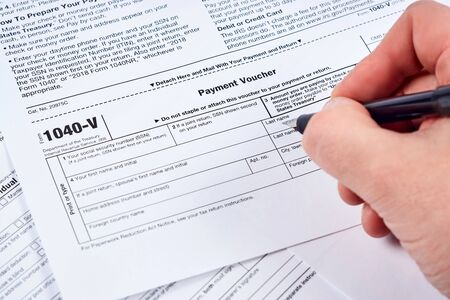 Tax payment form. Human fills out the 1040-v tax form on background other forms