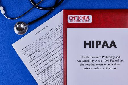 Health Insurance Portability and accountability act HIPAA, red folder with inscription confidential, medication request form and stethoscope on a blue velvet background. Close-up Reklamní fotografie