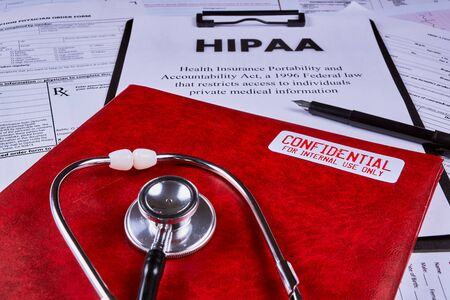 Health Insurance Portability and accountability act HIPAA, red folder with inscription confidential, pen and stethoscope on the medical documents background Stock fotó
