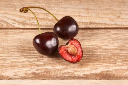 opened cherry with a ossicle, two cherries on wooden background Banque d'images