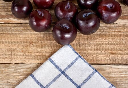red plums next to a doily on a wooden background