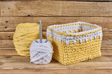 knitted basket with yarn and crochet on a wood background