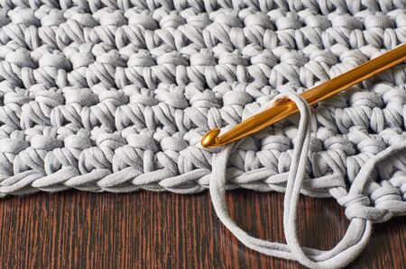 hook for knitting in a loop against the backdrop of a knitted carpet