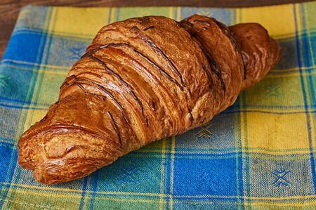 Chocolate croissant on a yellow-blue napkin on brown wooden background 版權商用圖片