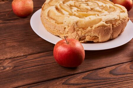 Red apples near apple pie on a brown wooden background Stockfoto