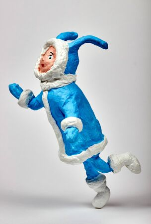 Christmas toy made of paper and cotton wool. Running girl in a blue hare costume. Close-up on white background. Stock Photo