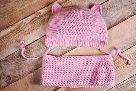 Children's knitted clothes. Pink baby cap with ears and pink snood on a wooden background. Flat lay