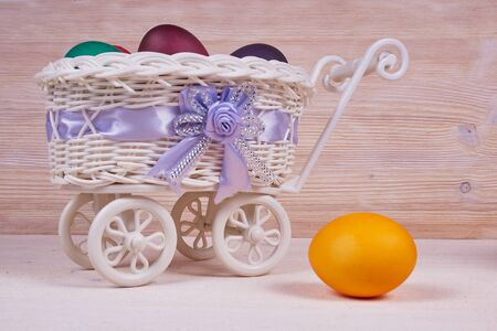 Easter composition. White basket on wheels with colorful Easter eggs on a wooden background